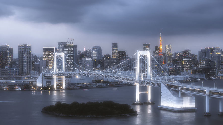 Illuminated bridge over river by buildings against sky