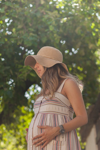 Low angle view of pregnant woman wearing hat while standing against trees