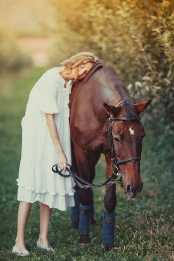 Woman leaning on horse in grass