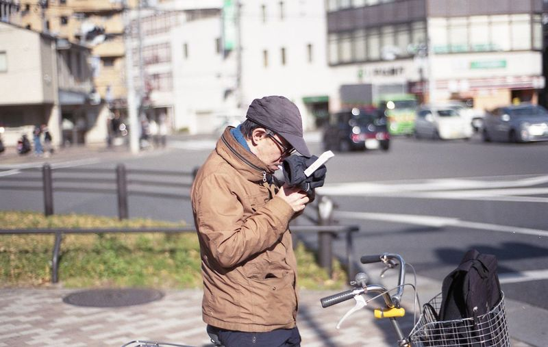 Man photographing with umbrella standing on street