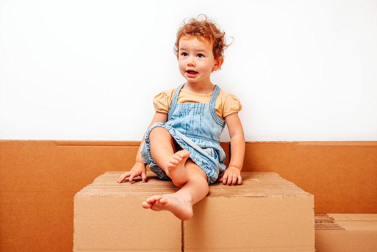 Full length of cute baby girl sitting in box