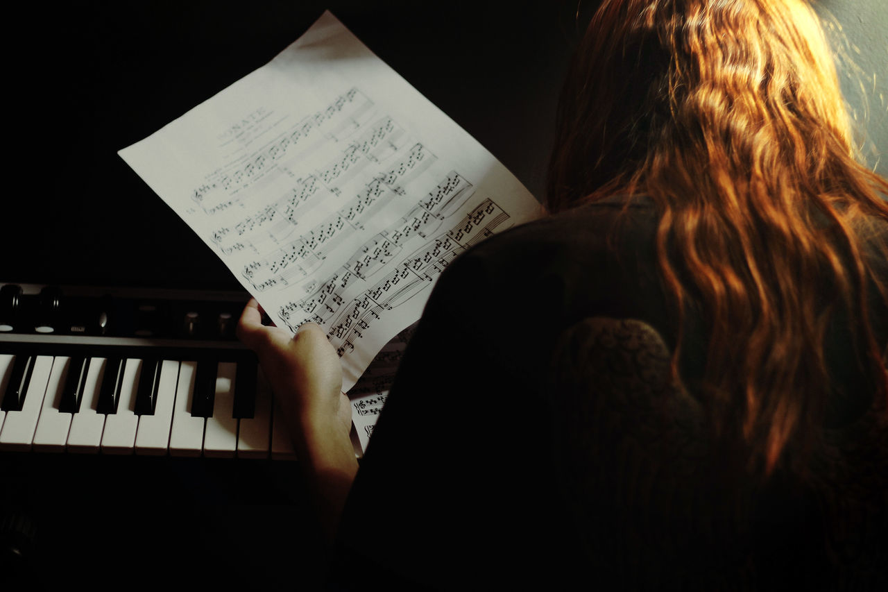 Woman By Piano Holding Musical Notes