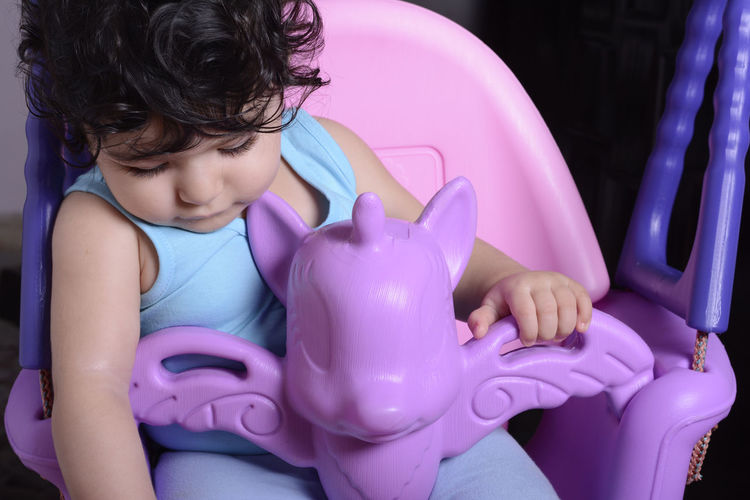 Cute baby girl sitting in swing at home
