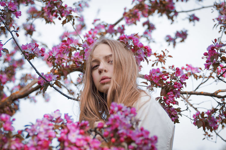 Portrait of young woman with pink cherry blossoms against trees