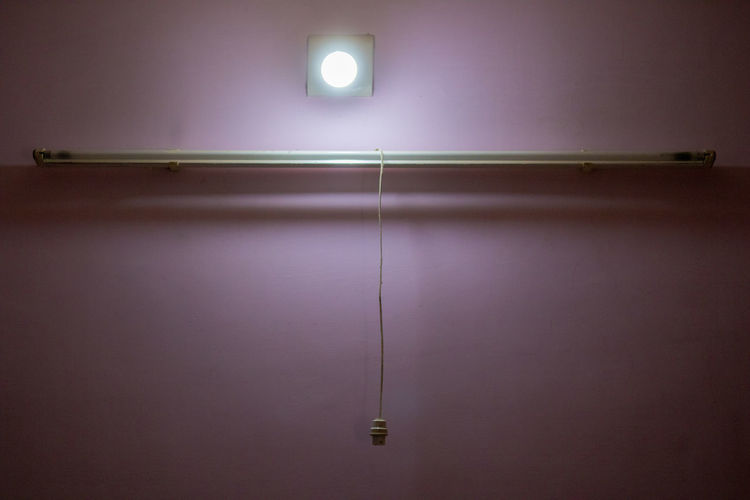 Illuminated light bulb on wall at home