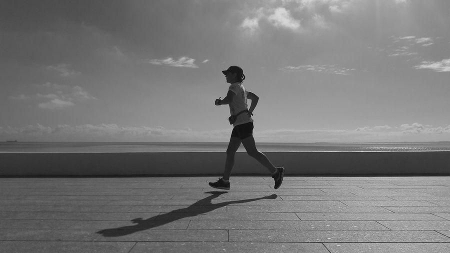 Side view full length of woman jogging at promenade against sky