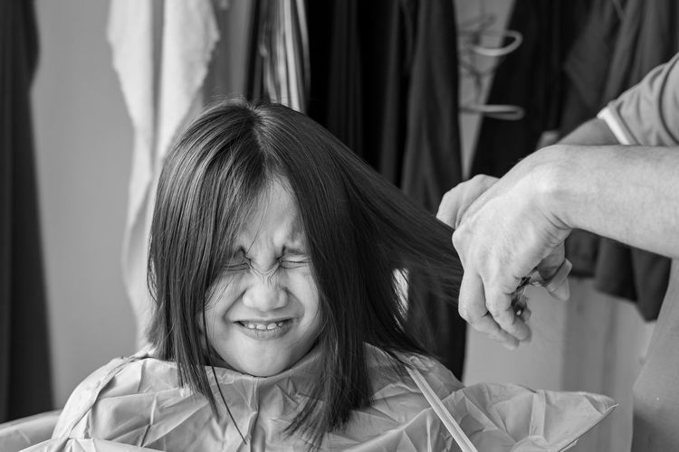 Asian young girl with funny expression is getting haircut at home. monochrome, black and white.