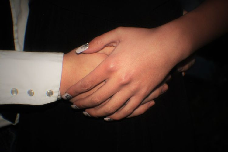 Cropped image of couple with holding hands