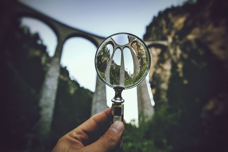 Cropped hand holding magnifying glass against viaduct bridge