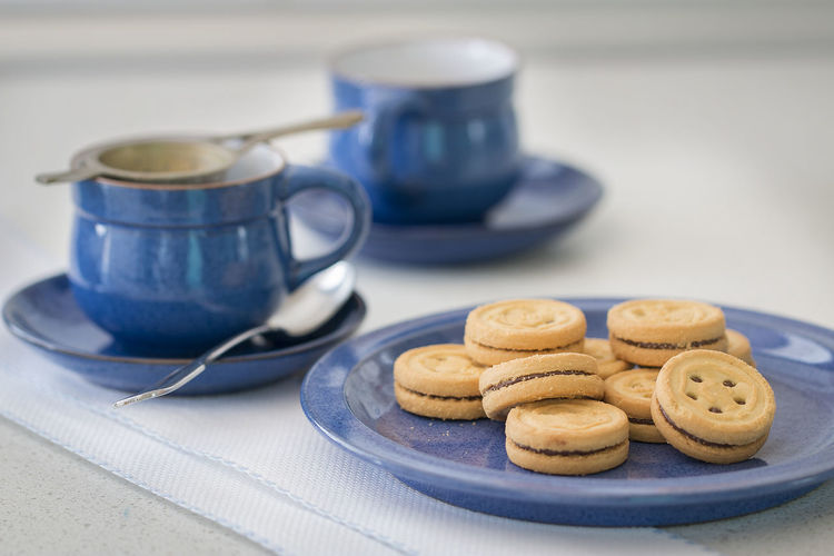 Some cookies on a blue two cups.