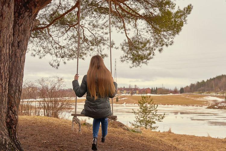 A young woman long blond hair on a wooden swings on a tree branch with icy river on the background..