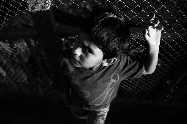 High angle portrait of boy standing by chainlink fence