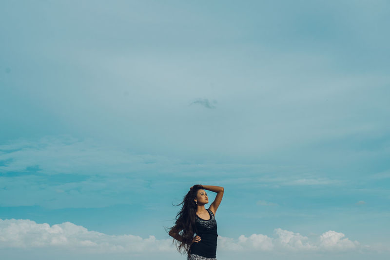 Young woman against blue sky