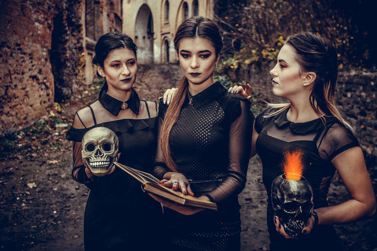 Digital composite image of woman with book and skull in hand standing outdoors