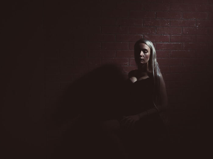 Woman with long hair sitting against wall in darkroom