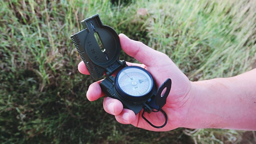Close-up of hand holding camera on field