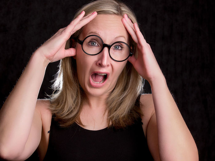 One Person Eyeglasses  Glasses Front View Young Adult Portrait Studio Shot Emotion Black Background Young Women Indoors  Hair Looking At Camera Headshot Mouth Open Mouth Blond Hair Surprise Hand Head In Hands Beautiful Woman Hairstyle Making A Face Human Face Frustration