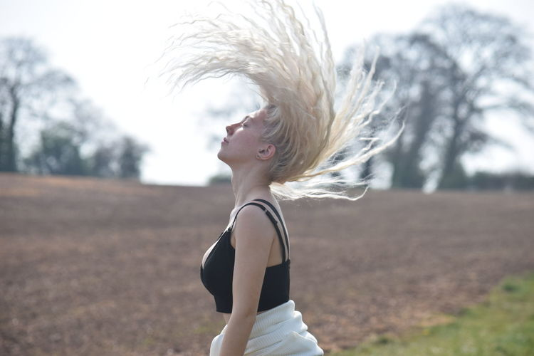 Young woman tossing hair while standing outdoors