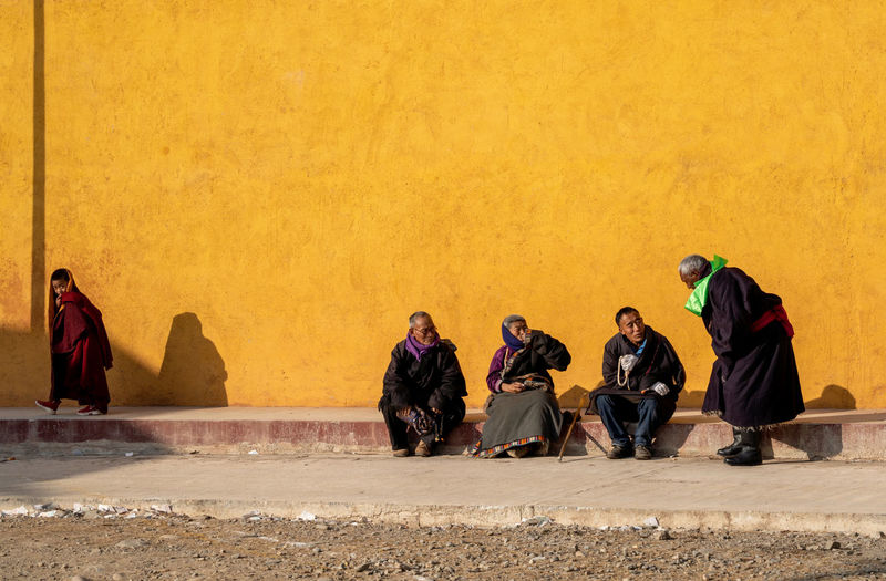 People sitting against yellow wall