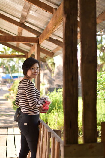 Adult Architecture Built Structure Casual Clothing Day Hair Hairstyle Looking At Camera One Person Outdoors Railing Side View Smiling Standing Striped Three Quarter Length Tree Women Young Adult