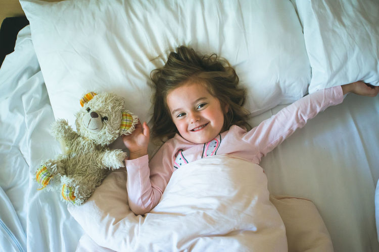 Little girl lying in a bed with teddy bear at the morning Lying Enoying 4-5 Years Relaxing Time Resting Teddybear Smiling Smile Pretty Toy Overhead View Cute Bedding Beautiful Beauty Home Happiness Happy Sheets Pillow Play Playing Daylight Day Morning Bedtime Bedroom Teddy Teddy Bear Bear Small Little Childhood Child Kid Girl Real People Indoors  One Person Bed Real Life Candid Moments Authentic Authenticity