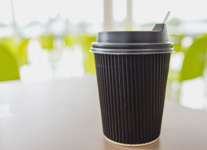 Hot coffee cup is black color and portable type. placed on a light brown table,bright background. Coffee Black Close-up Copy Space Day Disposable Disposable Cup Drink Drinking Glass Focus On Foreground Food Food And Drink Freshness Glass Household Equipment Indoors  No People Refreshment Single Object Snack Still Life Table Take Away Coffee