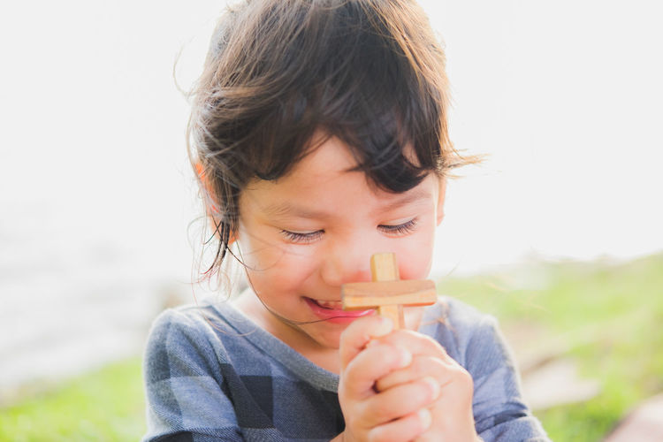 Close-up of smiling girl holding cross