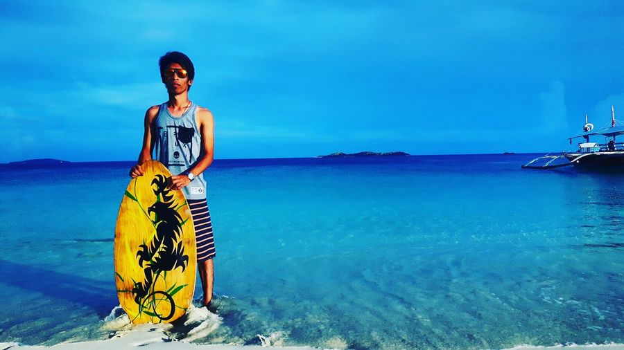 Young man standing with skimboard on shore at calaguas island