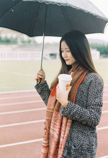 Young woman holding umbrella standing outdoors