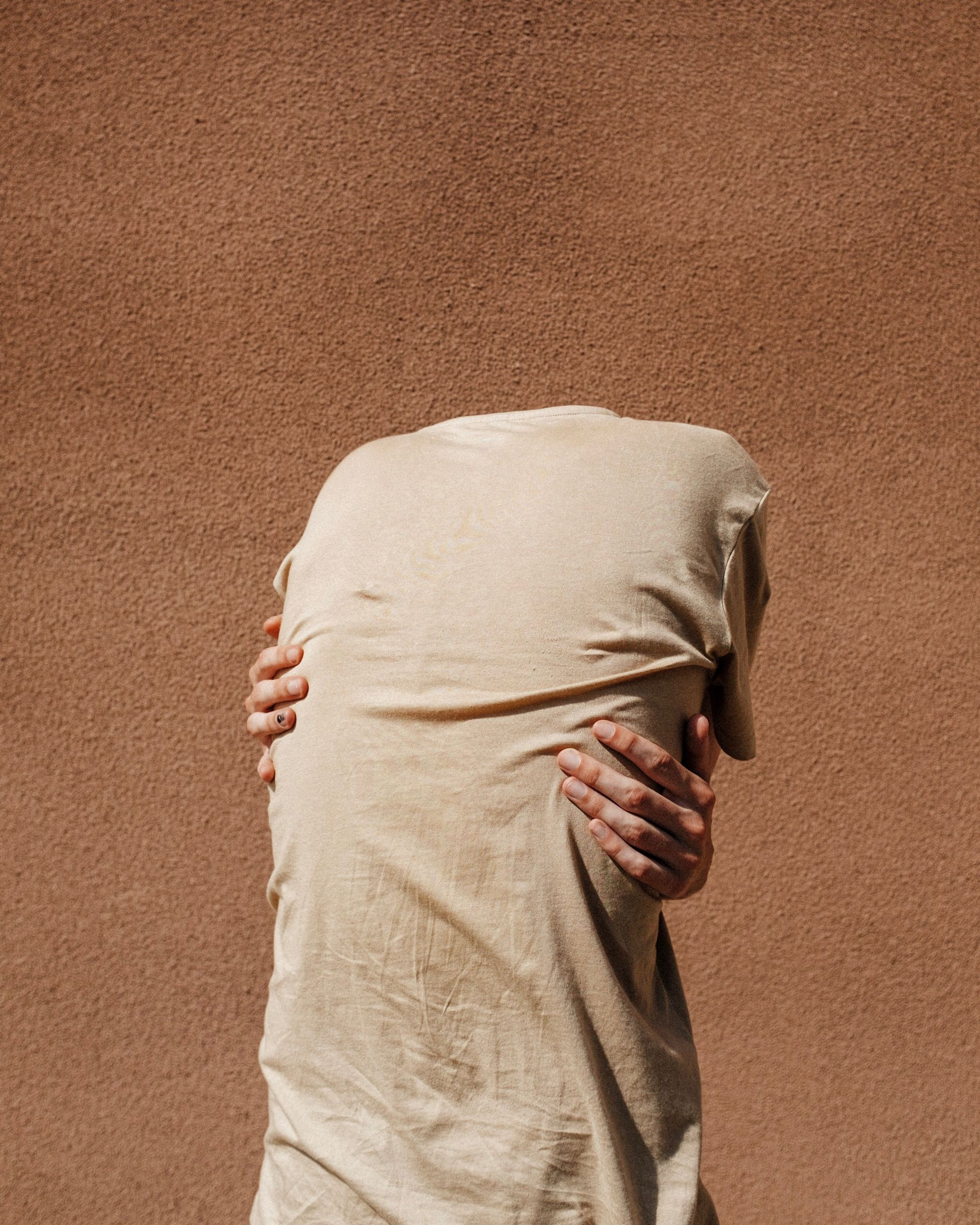 one person, obscured face, standing, adult, human body part, hiding, covering, indoors, unrecognizable person, young adult, waist up, day, textile, body part, casual clothing, three quarter length, nature, young women, depression - sadness