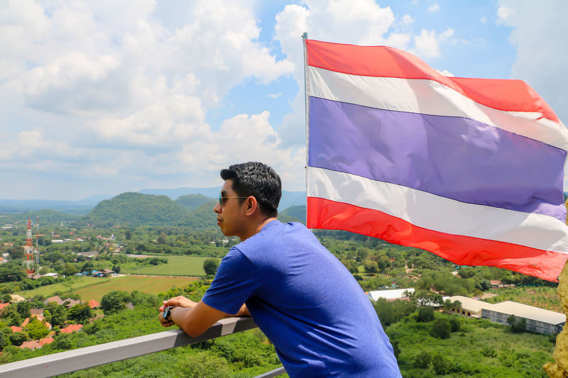Side view of man standing by thai flag at observation point