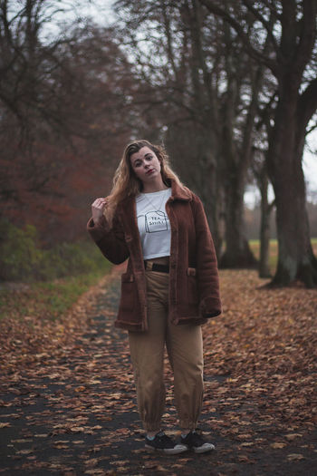 Full length portrait of woman standing in park during autumn
