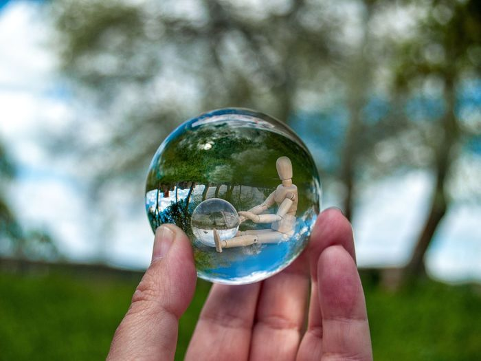 Close-up of hand holding crystal ball with reflection of figurine