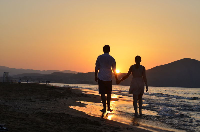 Rear view of silhouette couple standing on shore at beach during sunset