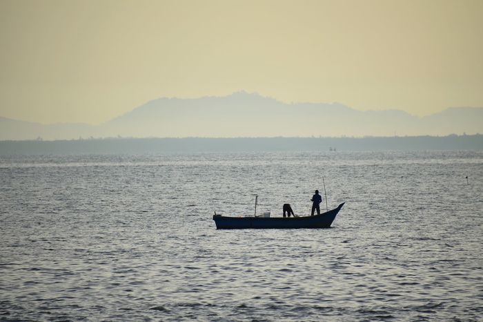 Fishing during sunrise. Nautical Vessel Water Sea Fisherman Occupation Sailing Sunken Silhouette Men Fishing