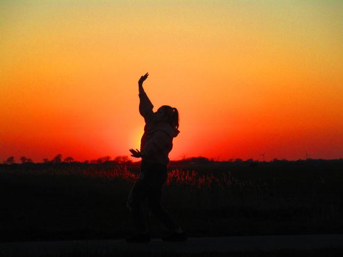 Girl dancing while walking on road against orange sky