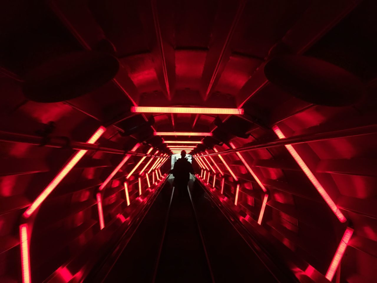 REAR VIEW OF PEOPLE WALKING IN ILLUMINATED SUBWAY TUNNEL