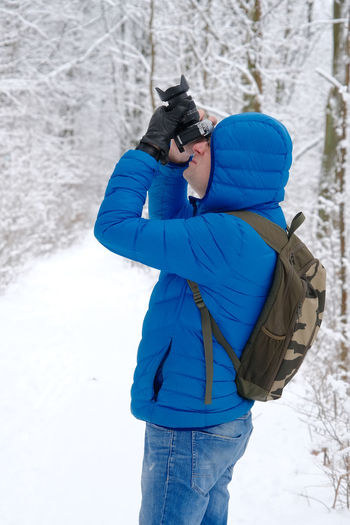 Man photographing on snow covered field