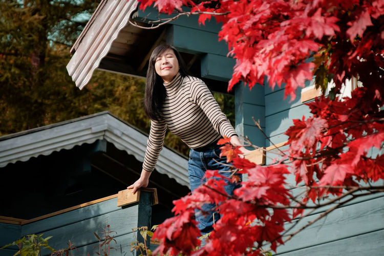 A Happy Woman Breathing Fresh Air in Autumn, Closed Eyes and Smiling in front of the House, Red Maple tree as foreground Plant Young Adult Building Exterior Built Structure Looking At Camera Nature Young Women Casual Clothing Front View Portrait Real People Change Standing Leisure Activity Clothing Day Women Lifestyles Outdoors Warm Clothing Smiling Breathing Space Freshness Morning