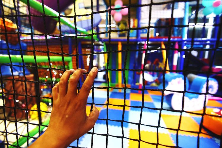 Close-Up Of Hand Holding Fence At Shopping Mall