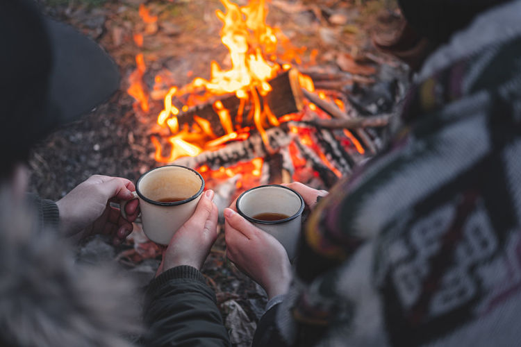 High angle view of couple having coffee in cups against campfire