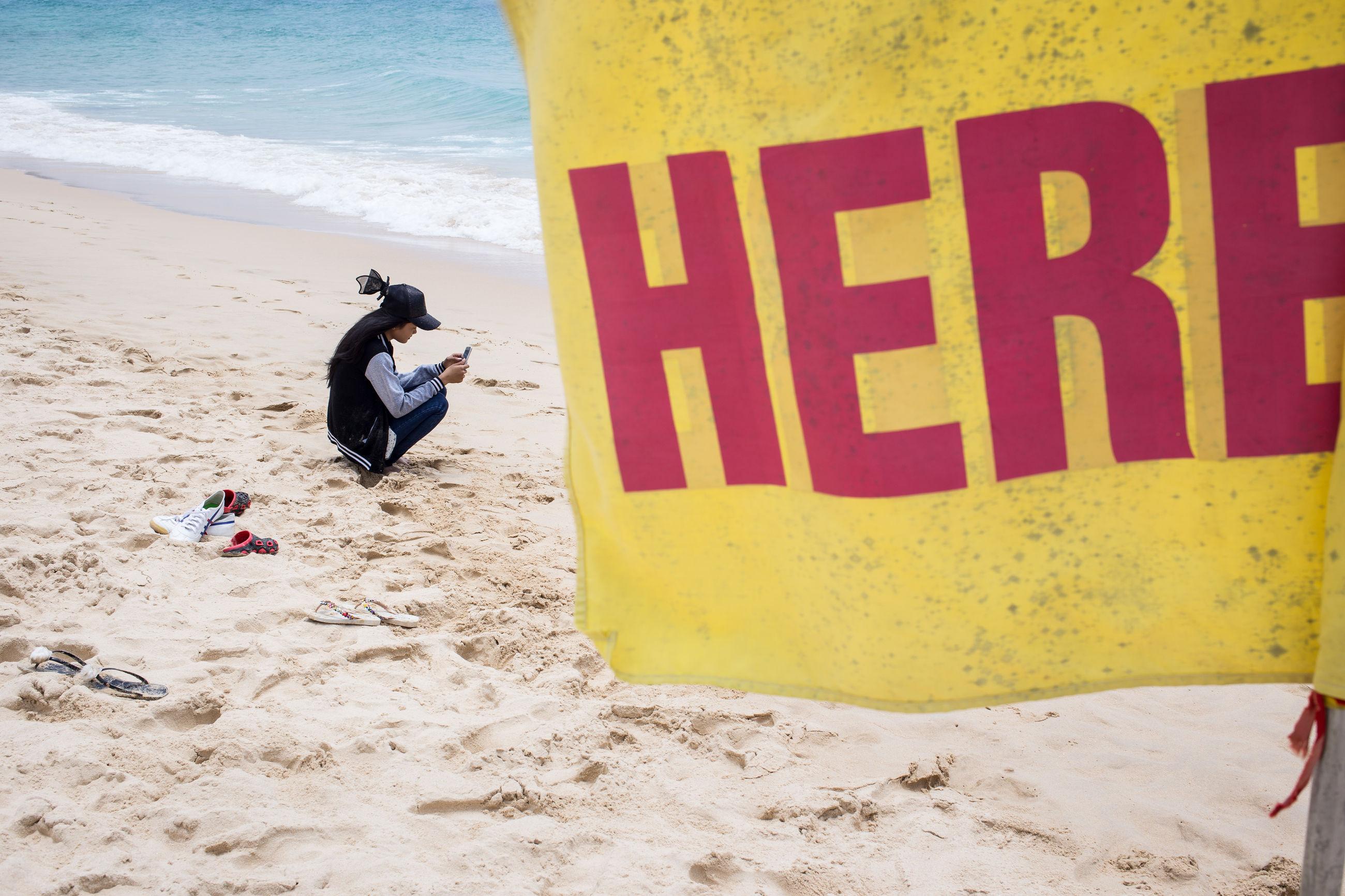 MAN WITH TEXT ON BEACH