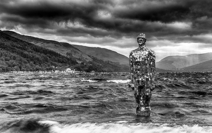 """Rob Mulholland's iconic Mirror Man statue (aka """"Still"""") at St.Fillans, on a stormy day on Loch Earn. Sad to see it is being removed. This was a test shot for a long exposure picture I published in back in June. Publishing it now as a tribute to Rob's classic piece of art. Loch  St.Fillan's St.Fillans Statue Beauty In Nature Cloud - Sky Day Lake Loch Earn Mirror Man Mountain Nature Outdoors Rob Mulholland Scenics Sky Still Stormy Water Waterfront Waves, Ocean, Nature"""