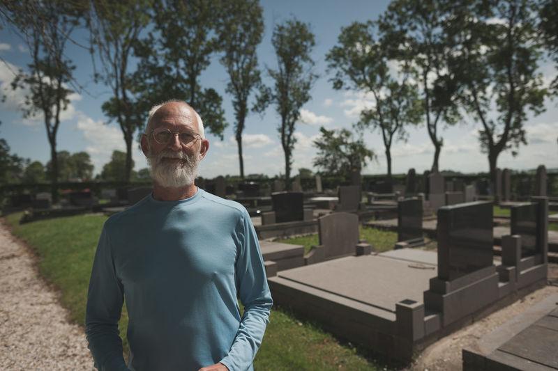 Senior Man Standing At Cemetery