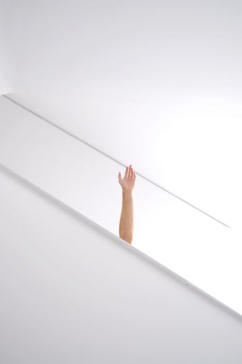 Cropped hand waving against white wall