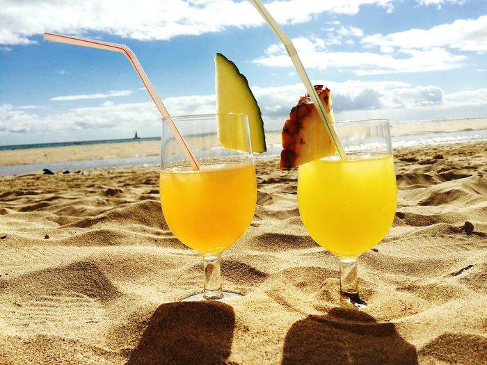 Close-Up Of Orange Juices On Sandy Beach