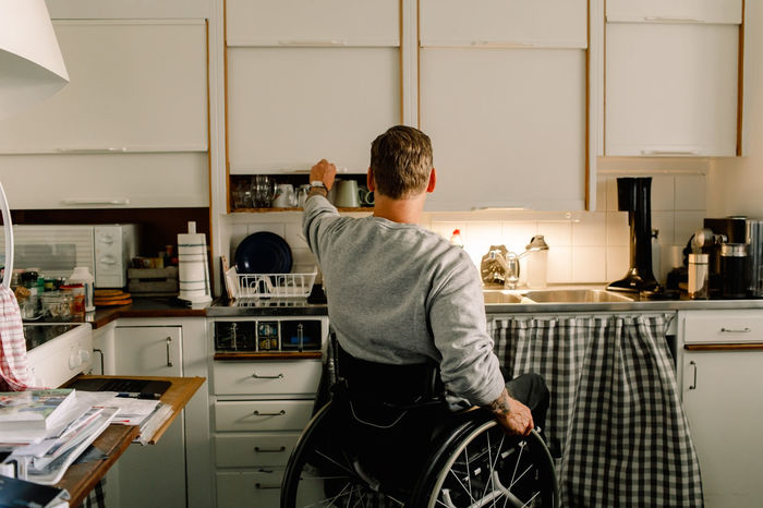REAR VIEW OF MAN SITTING BY TABLE AT HOME