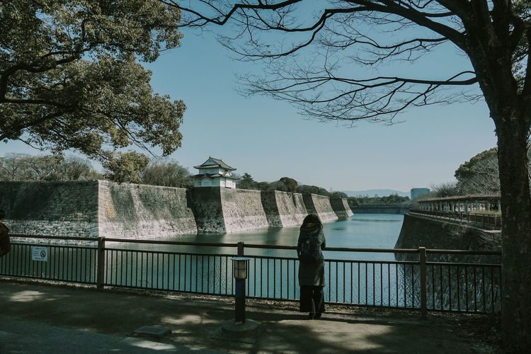 Man standing by railing against lake