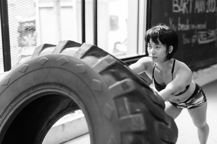 Young woman exercising with tire at home