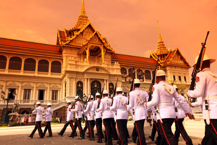 Army soldiers marching by historic building during sunset
